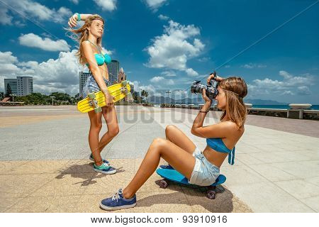 Portrait of beautiful skateboarding woman on skateboard and girl making photos at summer green park.
