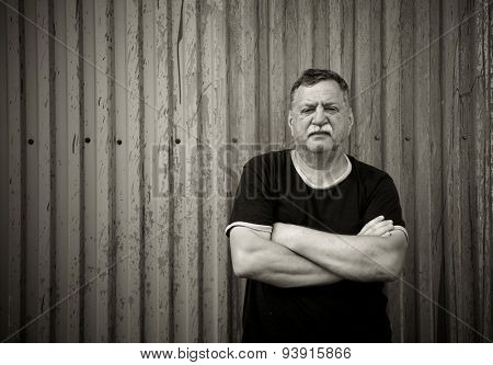 Mature mustachioed man sitting against the wall.