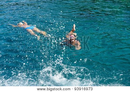 Women Are Swimming With Diving Goggles In The Sea.