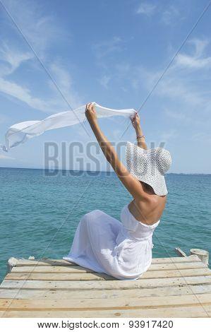Woman Waving A White Scarf On A Sea Dock