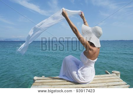 Woman Waving A White Scarf On A Sea Dock