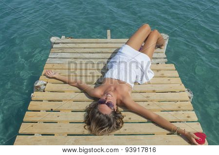 Girl In White Lying On The Dock Holding A Heart In Her Hand