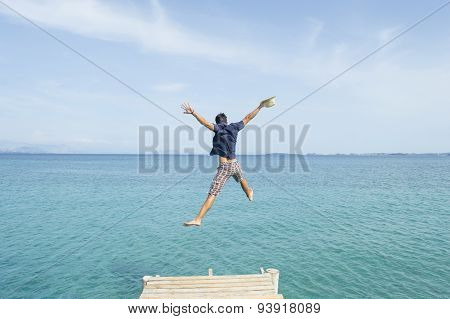 Young Man Jumping From The Dock Into The Sea