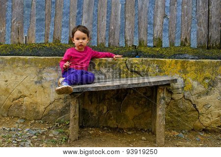 Two Years Old  Girl Sitting On Rustic Bench