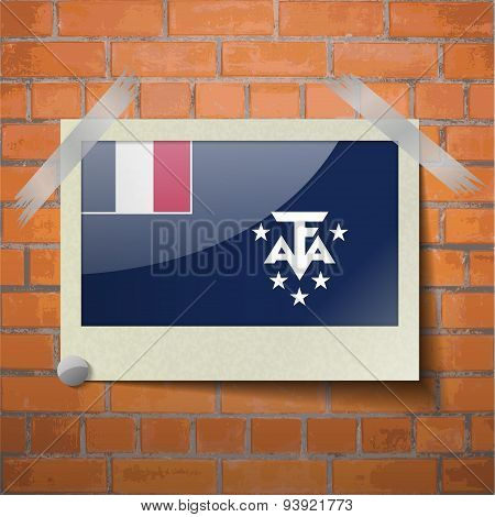 Flags Of French And Antarcic Scotch Taped To A Red Brick Wall