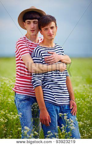Portrait Of Gay Couple In Love On Daisy Summer Field