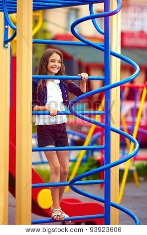 Cute Kid, Girl Climbs On The Stile At Playground