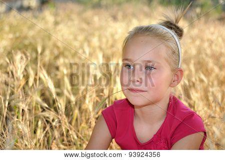 Cute happy little girl dreaming in wheat field