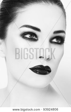 Black and white portrait of young beautiful woman with smoky eyes make-up