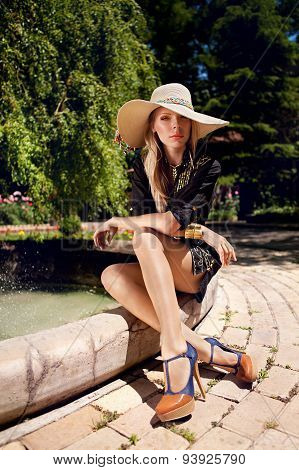 Attractive Girl In Srtaw Hat Sitting Near The Fountain