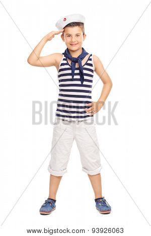 Full length portrait of a cute little kid in a sailor uniform saluting towards the camera isolated on white background