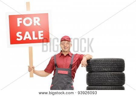 Cheerful male mechanic standing by a pile of tires and holding a big red for sale sign isolated on white background
