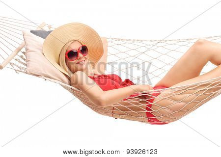Beautiful blond woman with a stylish hat and a red bathing suit lying in a hammock and smiling isolated on white background