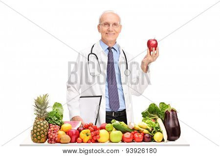 Mature doctor holding an apple and standing behind a table full of fruits and vegetables isolated on white background