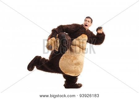 Terrified young man in a bear costume running away from something isolated on white background