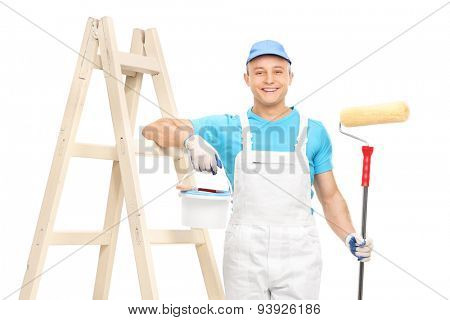 Young male house painter in a white clean jumpsuit holding a paint roller and leaning on a wooden ladder isolated on white background