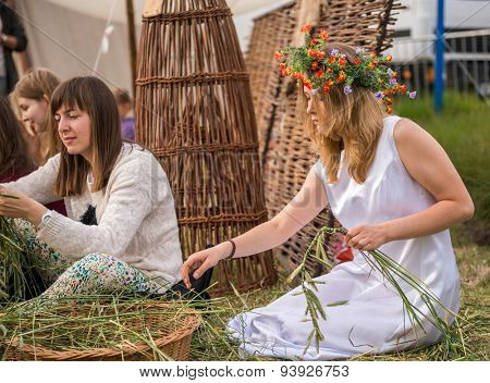 Warsaw, Poland -JUNE 20: Young girls make wreaths of flowers on festival of midsommar near the old town in Warsaw, Poland June 20, 2015
