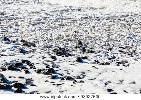 Stones In Foam On The Beach