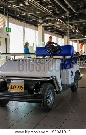 Interior Of Amsterdam Airport Schiphol. Passengers Near The Electric Vehicle For Transporting People
