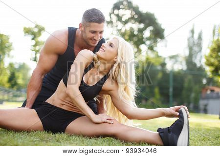 Fit Couple Doing Exercise Outdoor On Grass