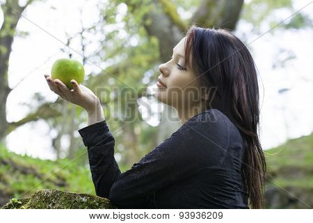 Young Woman With Apple. Nature Background
