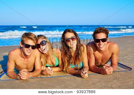Group of young friends couples portrait in beach lying on sand at summer vacation