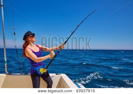 Beautiful woman girl fishing rod trolling in saltwater in a boat trolling