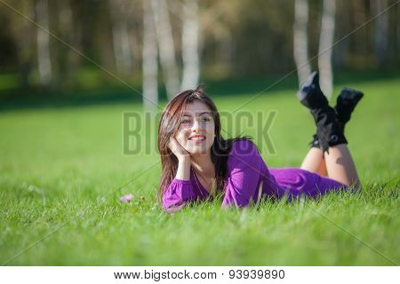 Beautiful young woman laying on grass