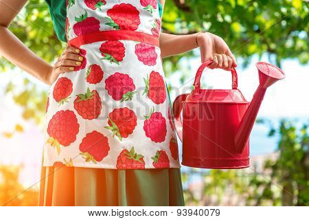 Woman holding a pink watering can