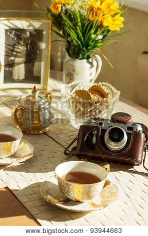 Cup of tea summer flowers old foto and vintage camera on wooden background