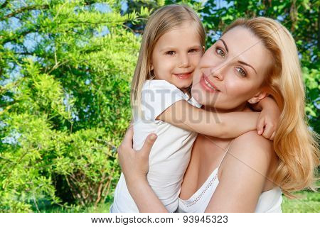 Mother holding her daughter in park