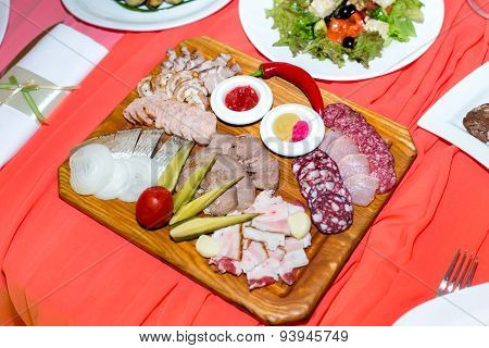 Cold Cuts On Wooden Plate On Banquet Table