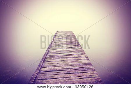 Vintage Filtered Picture Of Old Wooden Pier And Dense Fog.