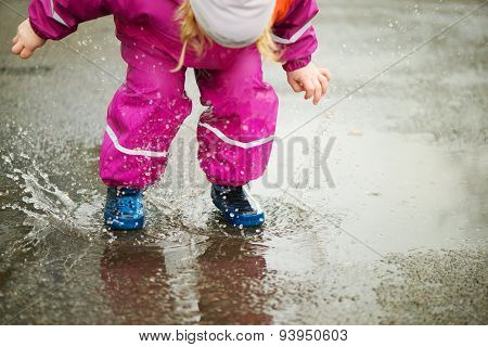 Little Happy Girl Jumping In Puddle