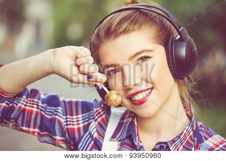 Portrait Of Cute Hipster Girl With Headphones And Lollipop.