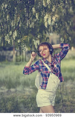 Hipster Girl With Headphones Dancing Under Tree.