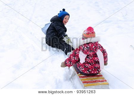 Cute Boy Pulling His Sister On Sled