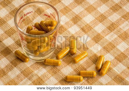 Glass Cup Of Herbal Medicine Capsules On Cotton.