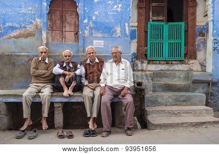 JODHPUR, INDIA - 16 FEBRUARY 2015: Four elderly men sit on stone bench on street in front of house.