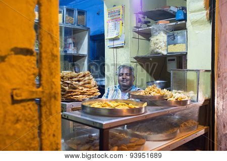 JODHPUR, INDIA - 16 FEBRUARY 2015: Vendor sits in store with food on metal plates.