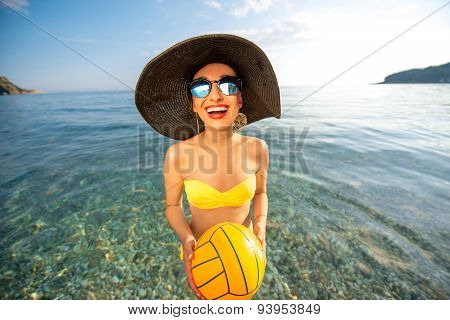 Woman with yellow ball in the sea