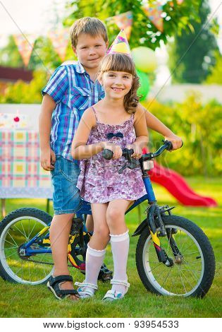 Two Happy Children Sitting On Bicycle