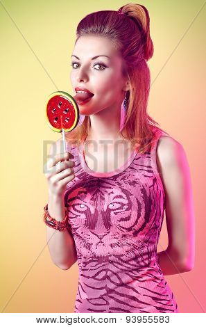 Portrait of mischievous redhead girl licking big lollipop. Fashion dressed