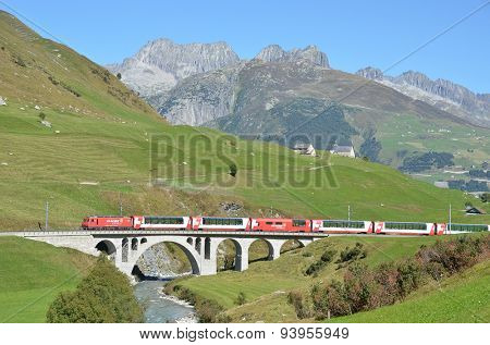 SWITZERLAND - SEP 16, 2012: Glacier Express of Matterhorn-Gotthard railway passing a bridge at Furka pass