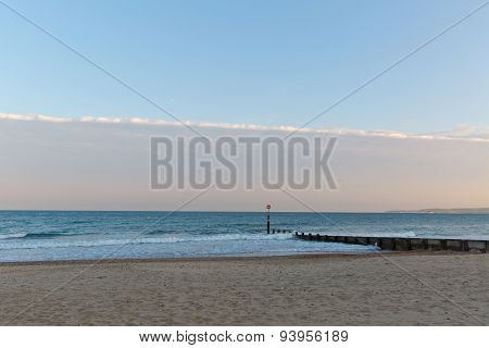 Golden Sunset Light Of A Pier Looking Towards The Sea At The Beach With Sand  And One Strip Of Cloud