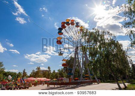 Ferris Wheel Against Blue Sky Background In City Park