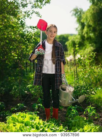 Smiling Girl Posing At Garden With Spade And Watering Can
