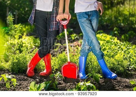 Closeup Of Two Girls In Gumboots Standing At Garden At Sunny Day