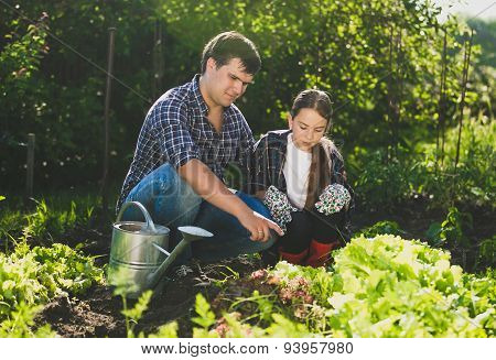 Man Sitting At Garden With Daughter And Teaching Her Horticulture
