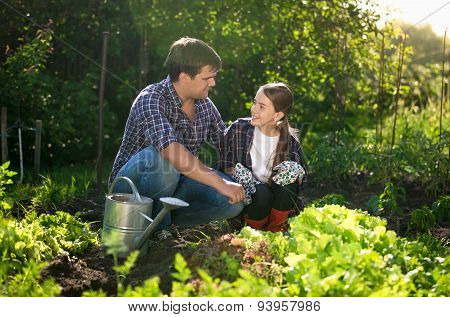 Smiling Father Teaching Daughter Horticulture At Garden